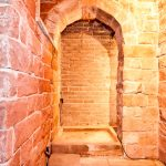 Photograph of a stone arched doorway with a shower drain inside