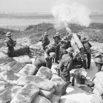 Artillery being fired at Fort Crosby, 1 August 1940, with soldiers standing by